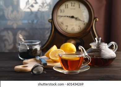 Teapot, cup and hot tea. Table with old clock