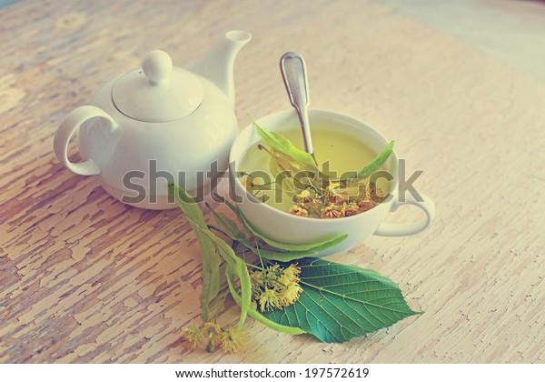 tetera y taza con té de lino y flores sobre mesa de madera