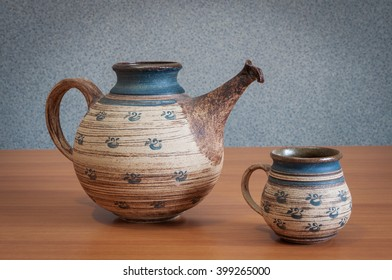teapot and cup on the table with a gray background