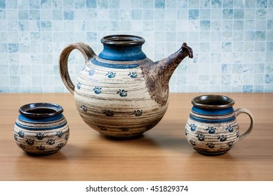 Teapot with cup on table in wood