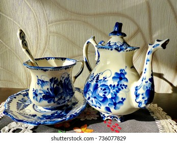 Teapot, cup with saucer and teaspoon. Things in Russian traditional Gzhel style. Closeup. Gzhel - Russian folk craft of ceramics and production porcelain and a kind of Russian folk painting.