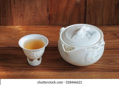 Teapot and cup of tea on a wooden background.