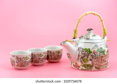 Teapot with cups on a pink background. White teapot with Chinese style painting.
