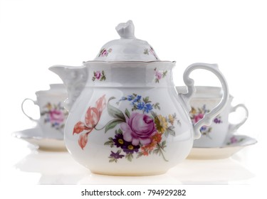 Teapot with cups on a white background. Selective focus.