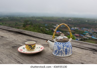 Teapot and cups on wood table with a good view.