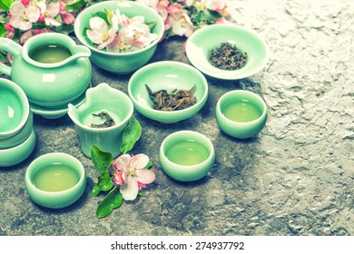 Teapot and cups with spring apple blossoms. Traditional chinese tea ceremony. Retro style toned picture.