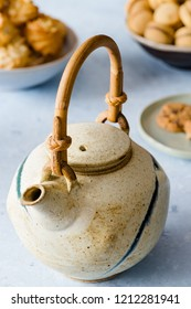 Teapot, different types of biscuits on a delicate blue background