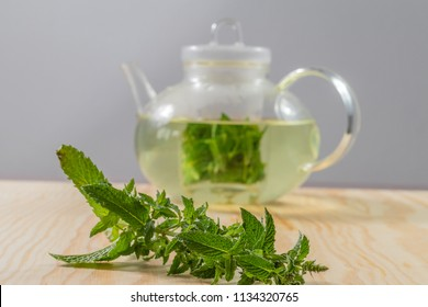 Teapot filled with pepermint tea on a wooden table