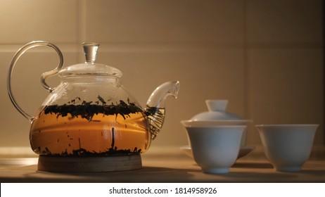Thé avec feuilles de thé fraîches à l'eau chaude et petites tasses sur la table de la cuisine. Concept. Gros plan sur une théière transparente en verre avec du thé noir en train de brasser, concept de cérémonie du thé.