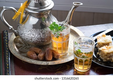 Teapot and glasses of Moroccan tea, together with dates and sweet baklava