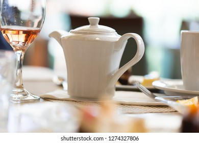 Teapot on table in luxury restaurant next to glass with rose wine. Low angle perspective focus on the teapot