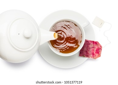 teapot pouring tea into cup on white table