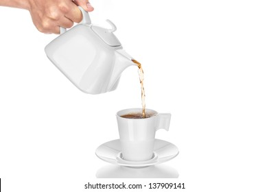Teapot pouring tea into cup, isolated on white background.