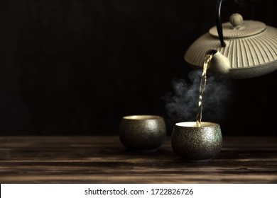 Teapot pouring tea into cups. Traditional japanese chinese iron teapot and ceramic teacups, asian tea set on dark background, copy space.