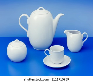 teapot, sugar bowl, cup, milk jug on light blue background