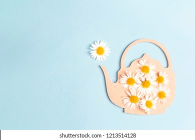 Teapot  symbol with chamomile flowers on a blue background. Chamomile come out of the teapot spout like steam. Chamomile tea concept. Flat lay, top view.