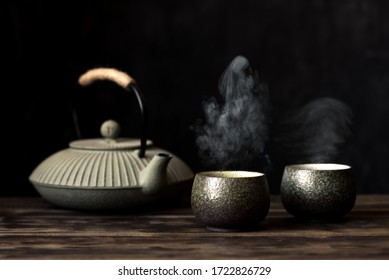 Teapot and tea cups with steaming fresh tea. Traditional japanese chinese iron teapot and ceramic teacups, asian tea set on dark background, copy space.