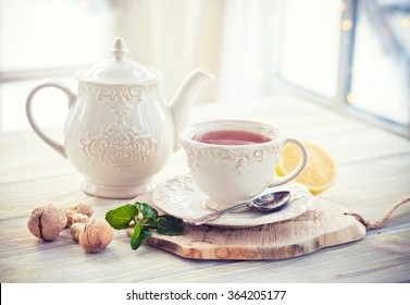 Teapot and teacup in vintage style and winter window