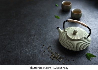 Teapot and Teacups on black background, copy space. Traditional Asian Tea Set -  iron teapot and ceramic teacups with green tea and tea leaves.
