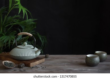 Teapot and Teacups on black background, copy space. Traditional Asian arrangement  for Tea ceremony -  iron teapot and ceramic teacups with tea.
