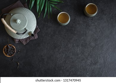 Teapot and Teacups on black background, copy space. Traditional Asian arrangement  for Tea ceremony -  iron teapot and ceramic teacups with tea, top view.