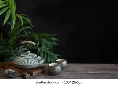 Teapot and Teacups on black background, copy space. Traditional Asian Tea Set -  iron teapot and ceramic teacups with green tea for tea ceremony.