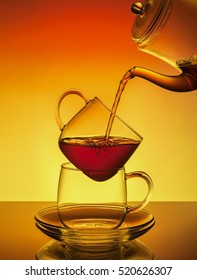 From a teapot transparent tea is poured into a transparent cup