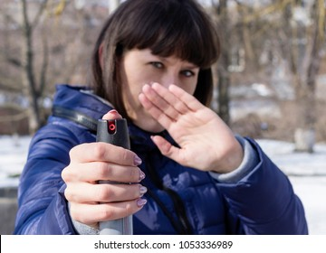 Tear gas or pepper spray in hand of young caucasian woman, means of self-defense in deserted park. Close-up, selective focus.