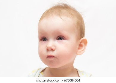 A tear runs down the cheek of a cute sad baby on a white isolated background