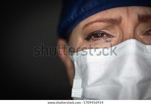Médica o enfermera cansada usando una máscara médica de fondo oscuro.