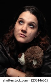 tearful woman holding the teddy bear of a child she lost due to miscarriage