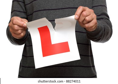 Tearing L plate after passing driving test against white background concept for success