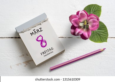 Tear-off calendar with International Women's Day 2019 (in German) on top on wooden background