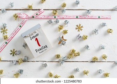 tear-off calendar surrounded by christmas decoration and with the 1st of january 2019 (in German) on top