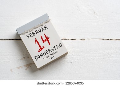 tear-off calendar with Valentine's Day 2019 (in German) on top on wooden background