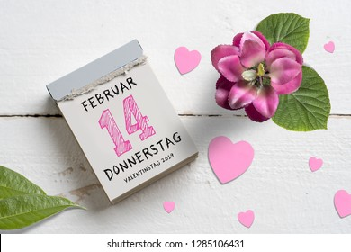 tear-off calendar with Valentine's Day 2019 (in German) on top,  surrounded by hearts on wooden background