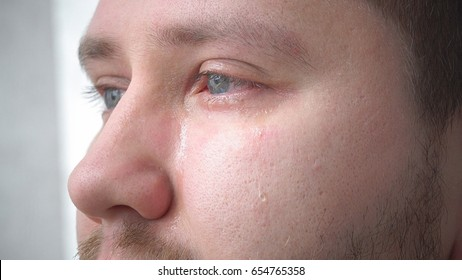 Tears in the eyes of an adult man crying closeup