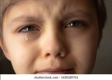 Tears in the eyes of a child. The boy is crying and a tear runs down his cheek. Close-up.