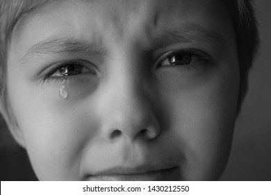 Tears in the eyes of a child. The boy is crying and a tear runs down his cheek. Close-up. Black and white photo.