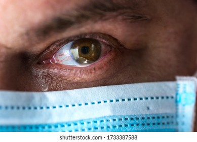 Tears in eyes of crying male doctor  in  mask.  Tired doctor in medical mask is looking at camera with worry, frustration, tiredness and exhaustion deep feelings. Eyes Close up . Selective focus