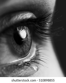 Tears on eyes. Open expressive look eyes with teardrop on the eyelashes macro close-up black and white. Sensual expressive sad  artistic image.
