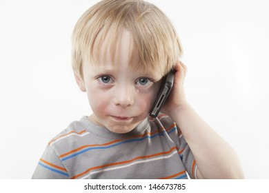 A teary, crying sad 4 year old boy using a mobile phone against a white background