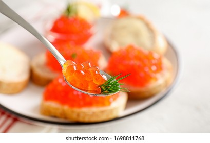 Teaspoon with red caviar and rosemary on white table background.