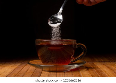 Teaspoon with sugar and tea. Crystals pour in a cup. The concept of a diet without sweets or drinks with sugar.