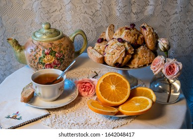 Teatime table with teapot, scones, pink roses and a sliced orange. A cup of tea in a traditional white china teacup and saucer on a crochet doily and embrodered napkin with a white lace background.