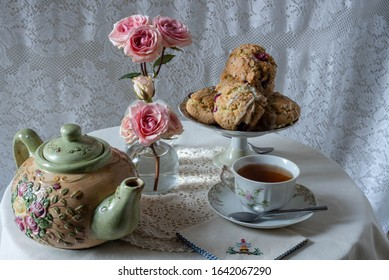 Teatime tablel with a plate of cranberry scones, floral green and yellow teapot, cup and saucer of tea with spoon and embroidered napkin set on a white tablecloth and doily and small pink roses.