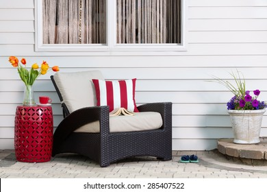Teatime taking a relaxing break on the outdoor patio in a comfortable deep seating armchair with colorful spring flowers enjoying the seasonal sunshine
