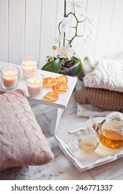 Tea-tray with hot grass drink, knitting clothes, dry oranges, candles and flowers. Winter mood. Cozy style