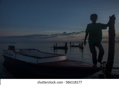 Tebah Batang,Lahad Datu,Sabah,Borneo,Mac 2014:-Silhouette of a young group sea gypsies boy standing at wooden boat during fishing.Sea gypsy people live nomadic in the ocean and survive for their life.