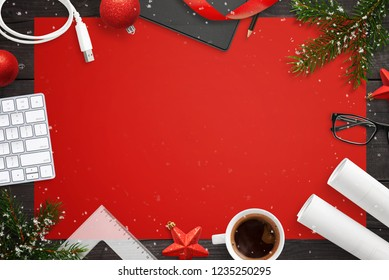 Tech devices and Christmas decorations on deks. Red table cloth in background with copy space. Project papers, cup of coffee, keyboard, usb cable, glasses and folder beside.